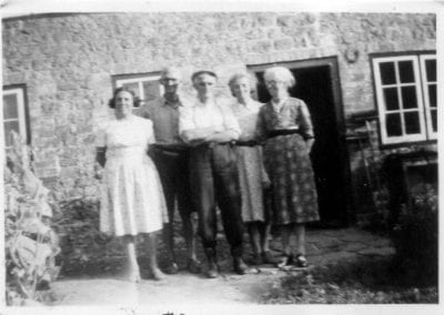 Five people outside cottage